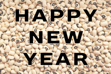 eyed: HAPPY NEW YEAR text written over a dried black eyed beans background, food considered to bring good luck