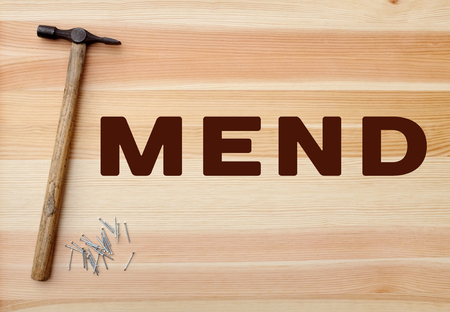 mend: Hammer and metal panel pins with MEND concept written on a wooden background