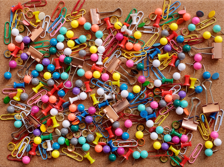 drawing pins: Background of colorful drawing pins, paper clips and metal binder clips on a cork board