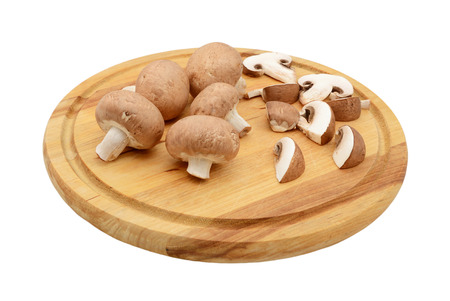 halved  half: Whole and sliced chestnut mushrooms arranged on a wooden cutting board, isolated on a white background