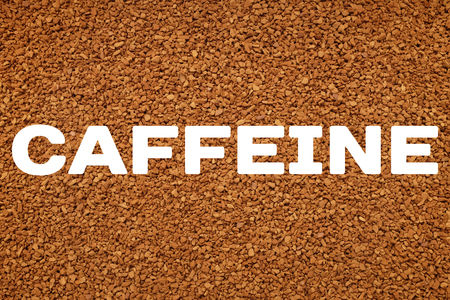 caffeinated: CAFFEINE text written over background of instant coffee granules