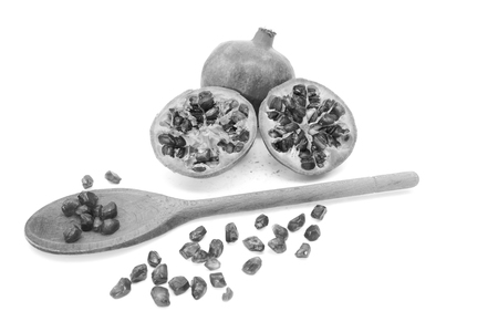 Whole pomegranate and two cut halves with some seeds removed with a wooden spoon, isolated on a white background. Stock Photo