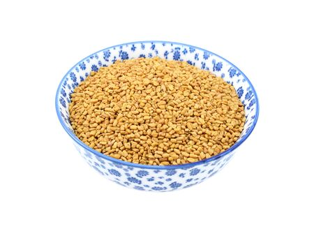 Fenugreek seeds in a blue and white porcelain bowl with a floral design, isolated on a white background