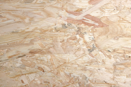 Smooth pale background of OSB - oriented strand board - wooden strips combined with adhesive to make sheet building material. Stock Photo