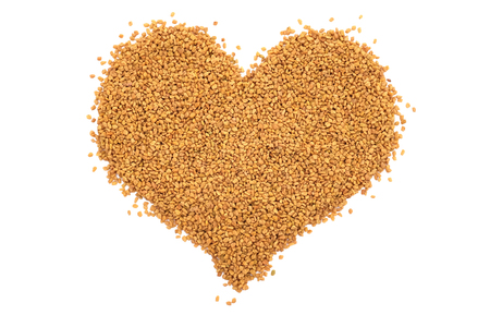 Dried fenugreek seeds in a heart shape, isolated on a white background