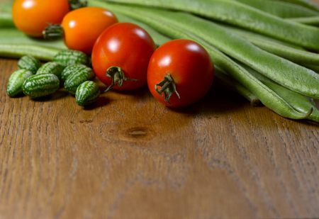 Cucamelons, orange and red tomatoes in selective focus against fresh green runner beans on wood with copy space