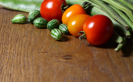 Cucamelons in selective focus with red and orange tomatoes, and green runner beans on wood with copy space