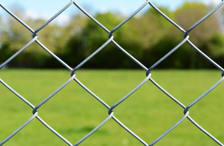 Metal chain link fencing in selective focus. Beyond the secure fence lies an empty green field, lined by trees.