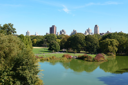 NEW YORK - OCTOBER 20, 2017: Turtle Pond in Central Park, Manhattan. Tourists enjoy early fall sunshine in the 843 acre urban park. Skyscrapers of the city can be seen above the tree line.