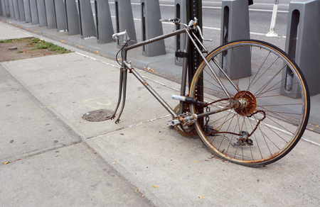 Broken, rusty bicycle with missing front wheel and dropped chain locked to a metal pole on a sidewalk Stock Photo