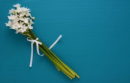 Small bunch of fragrant white narcissi, tied with a white ribbon on a blue painted background - with copy space Stock Photo