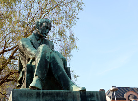 HELSINKI, FINLAND - May 13, 2018: Statue of Aleksis Kivi in Rautatientori Square, Helsinki. Kivi was a Finnish author who wrote the first significant novel in the Finnish language. The statue was sculpted by Wäinö Aaltonen in 1939.