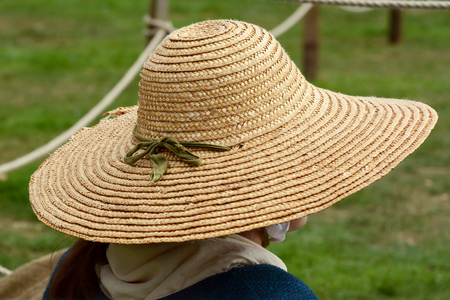 Woman wearing a traditional straw hat, her face hidden at a Medieval fair