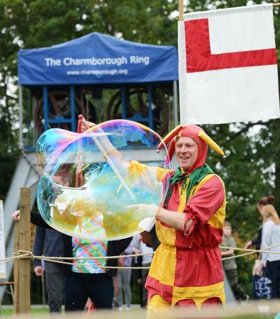 TONBRIDGE, ENGLAND - SEPTEMBER 8, 2018: Bosco the Jester entertains the audience at the Tonbridge Castle Medieval Fair, producing a large soap bubble 写真素材 - 117148935