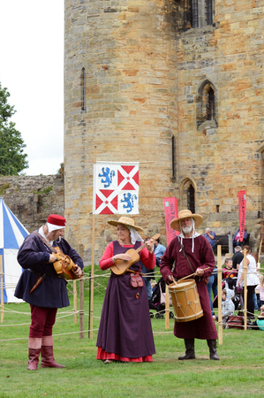 TONBRIDGE, ENGLAND - SEPTEMBER 8, 2018: Three musical minstrels perform on authentic instruments from the Middle Ages - hurdy gurdy, guitar, drum - at a medieval fair