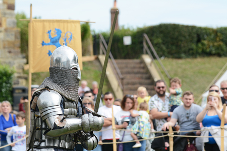 TONBRIDGE, ENGLAND - SEPTEMBER 9, 2018: Medieval knight in full battle regalia with a chainmail visor brandishes his sword at a battle re-enactment in front of a crowd at Tonbridge Castle