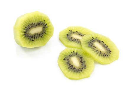 Peeled half kiwi fruit with green flesh and lots of black seeds with three juicy slices on a white background