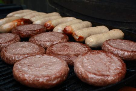 Rows of burgers and sausages starting to cook and brown on a barbecue grill Imagens