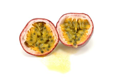 Passion fruit cut in half to reveal juicy yellow pulp around seeds, on a white background