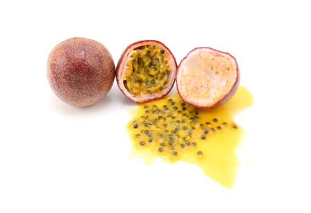 Whole and halved purple passion fruits with spilled juice and sweet seeds, on a white background