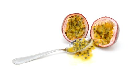 Spoon scooping out pulp and seeds from a purple passion fruit cut in half, on a white background