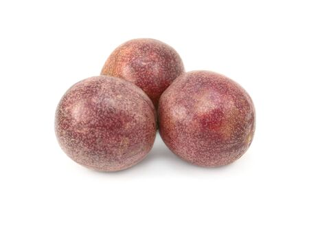 Three whole passion fruits with speckled purple skins, on a white background