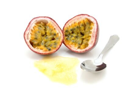 Passion fruit cut in half with juicy pulp and seeds, ready to eat with a spoon, on a white background