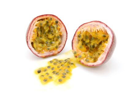 Passion fruit cut in half with juicy yellow pulp and seeds, on a white background