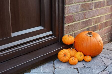 Large orange pumpkin and mini pumpkins as seasonal decorations at the front door of a house