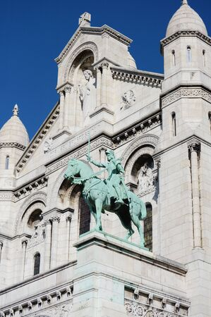 Joan of Arc bronze equestrian statue on the facade of the Sacre Coeur basilica, with the limestone architecture of the church beyond 版權商用圖片