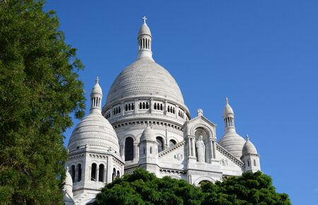 Dome of the Sacre Coeur basilica in Paris rises above trees against a blue sky, showing detailed architecture