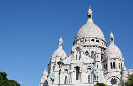 Imposing view of the Basilica of the Sacred Heart of Paris at Montmartre against deep blue sky. Romano-Byzantine architecture constructed in travertine limestone.