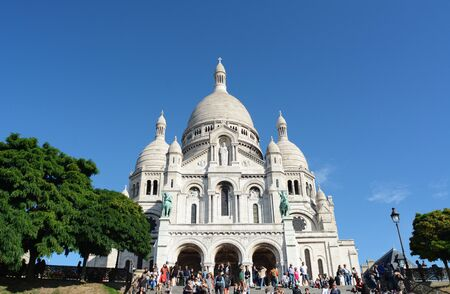 PARIS, FRANCE - SEPTEMBER 16, 2019: Basilica of the Sacred Heart of Paris at the top of Montmartre, surrounded by tourists on September 16, 2019
