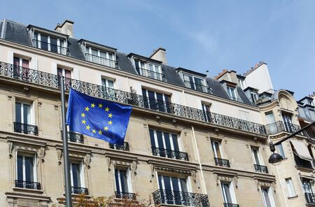 PARIS, FRANCE - SEPTEMBER 16, 2019: EU flag with 27 stars representing the states of the European Union, flies against a backdrop of housing in Paris on September 16, 2019 新聞圖片