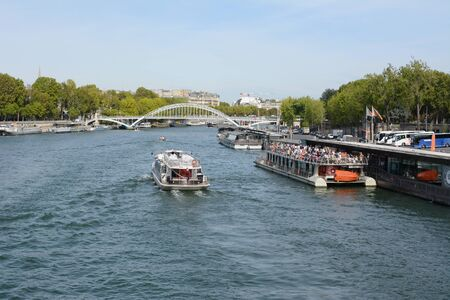 PARIS, FRANCE - SEPTEMBER 16, 2019: Tourist river cruise ferry full with passengers at the Port de la Bourdonnais among other river traffic on September 16, 2019. Seen from Jena bridge, looking towards the Debilly footbridge.