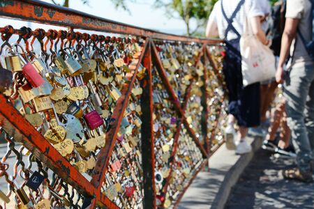 PARIS, FRANCE - SEPTEMBER 16, 2019: Numerous padlocks and combination locks fixed to the fence at the Sacre Coeur in Paris. Tourists lean on the fence in the background on September 16, 2019.