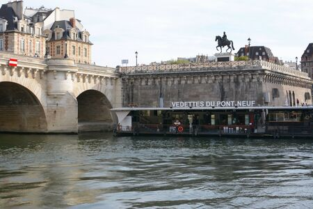 PARIS, FRANCE - SEPTEMBER 16, 2019: Vedettes du Pont Neuf sightseeing Seine cruise boat station at the New Bridge in Paris on September 16, 2019. Equestrian statue of Henri IV stands on street the above the river.