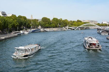 PARIS, FRANCE - SEPTEMBER 16, 2019: Tourist boat and Batobus ferry sail the Seine river, near the Debilly footbridge in Paris on September 16, 2019. Ferries are moored at the riverbank, which is lined by green trees.