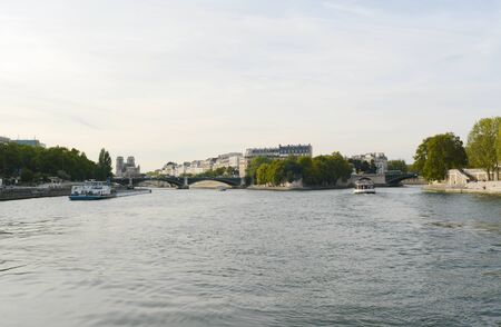 PARIS, FRANCE - SEPTEMBER 16, 2019: View northwest on the Seine towards the damaged Notre Dame cathedral on September 16, 2019. Cargo boat and ferries sail away from Ile St Louis, with the Pont de Sully spanning the river. Editöryel