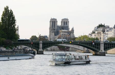 PARIS, FRANCE - SEPTEMBER 16, 2019: Pont Sully bridge spans the river Seine in Paris. Cargo boat and Batobus passenger ferry sail the river on September 16, 2019. In the background the damaged Notre Dame is half-covered with scaffolding after a major fire 新聞圖片