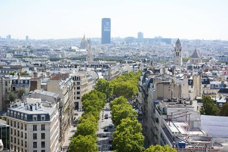 PARIS, FRANCE - SEPTEMBER 16, 2019: Cityscape of Paris from the top of the Arc de Triomphe along Avenue Marceau. View southeast across the city shows church spires and domes, and the Tour Montparnasse rising above the buildings on September 16, 2019.