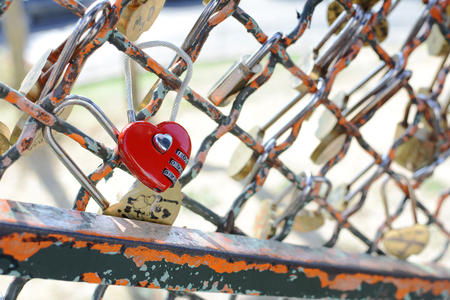 Red heart-shaped combination padlock fastened to metal fence near the Sacre Coeur basilica in Paris, France 新聞圖片