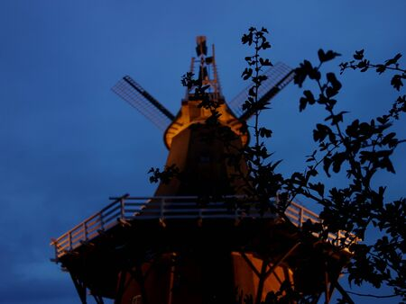 One of the twin mills of Greetsiel at night with twigs in the foreground 版權商用圖片 - 132063815