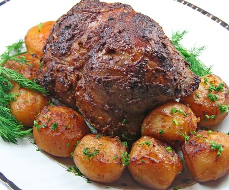 Roast leg of lamb with potatoes and dill on white plate photo
