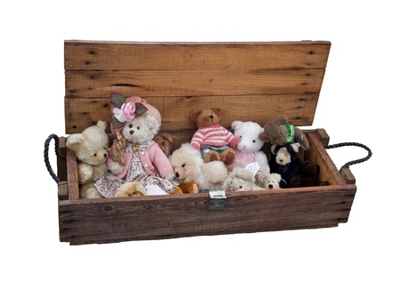 Old wooden box with vintage teddy bears at white background photo