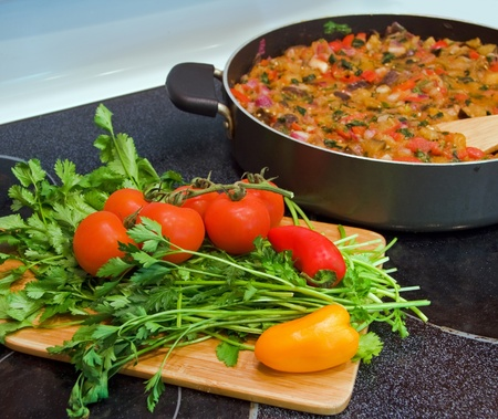 Stove top with vegetable stew in  frying pan and cutting board with vegetables and herbs