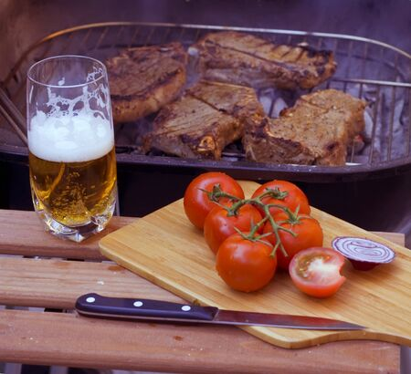 Stilleven met glas bier, steaks op de grill en tomaten Stockfoto