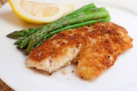 Closeup of fried breaded tilapia fillet with asparagus and lemon on white plate Imagens