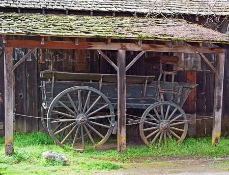 Retro wooden historical wagon under old wooden shed Фото со стока