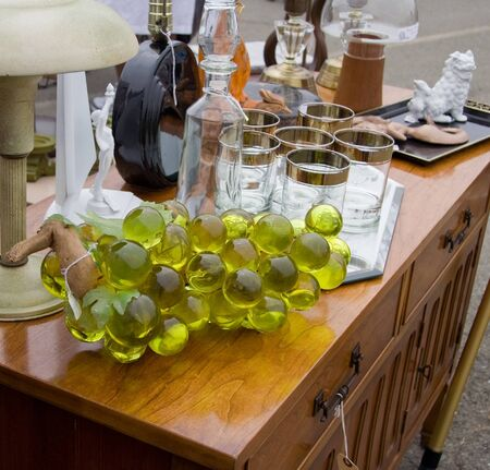 Table with different types of glass items at flea market photo